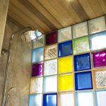 Интериорен дизайн на душ кабина с цветни стъклени тухлички, дървена обшивка на тавана във вила сауна от НП Архитекти