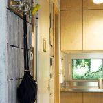 Интериорен дизайн на модерен кухненски бокс със шкафове от шперплат, иновативни осветителни тела, закачалка за дрехи и видими тухли във вила сауна от НП Архитекти