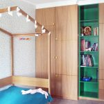 Modern interior design of a colorful child's girl bedroom with house bed, flower wallpaper and built-in wardrobes in apartment DNBD01 by NP Architects
